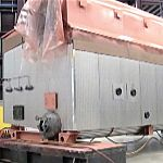 Two operators move a new 100-ton boiler from bay-to-bay in a manufacturing facility.